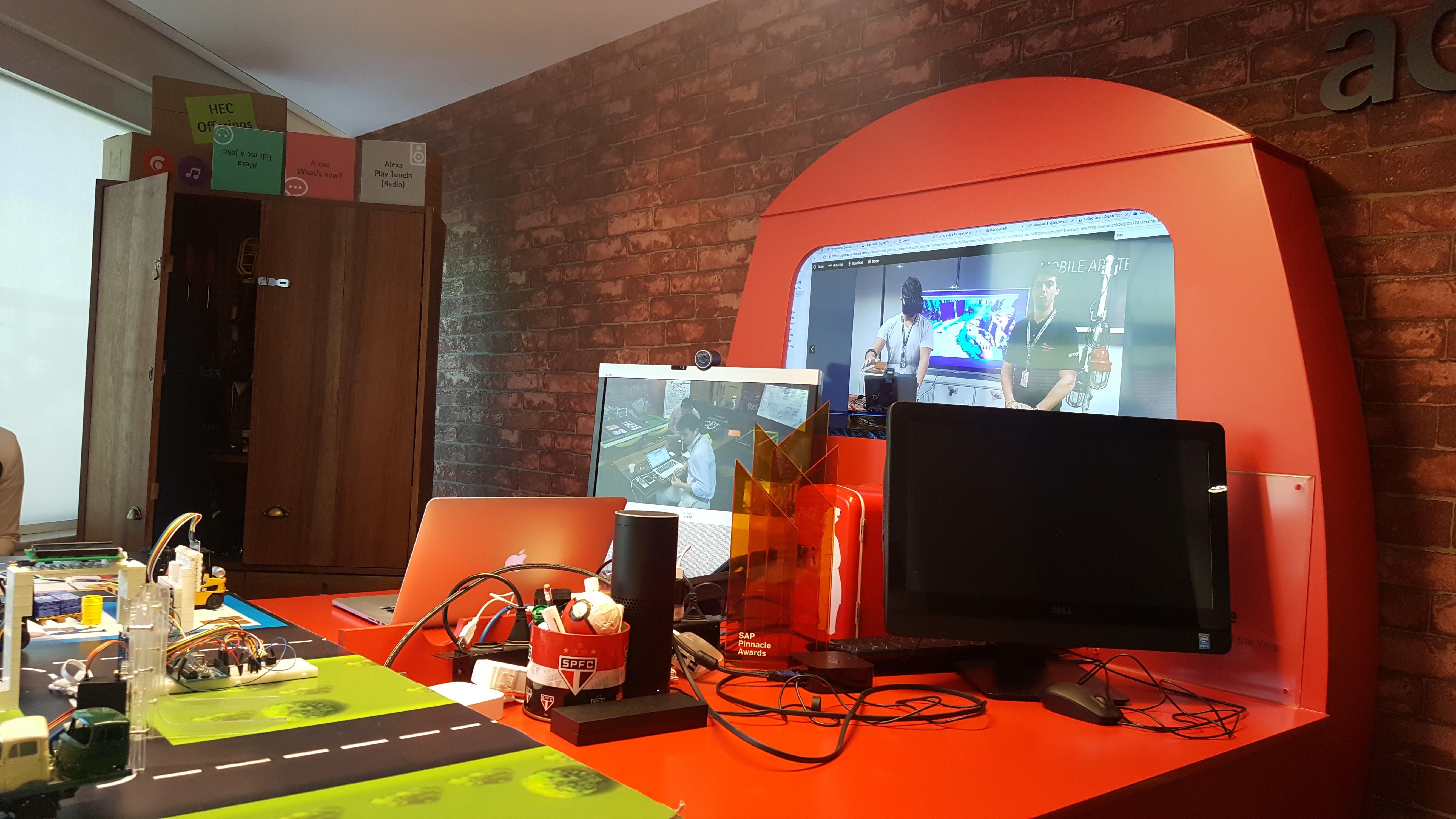 A Garagem da Accenture, com maquete do Market Place com soluções de logística com imagens ao vivo ao fundo do time de inovação em Recife.